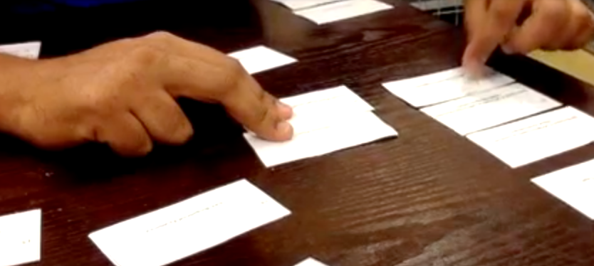 hands touching paper cards on a desk