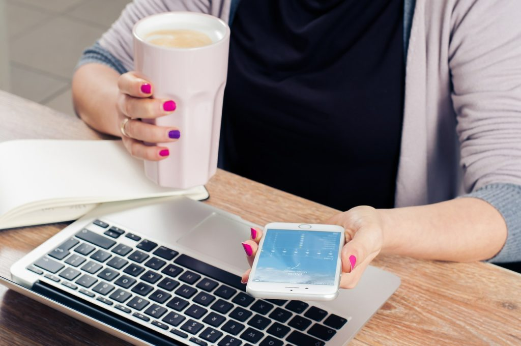 A woman, holding a cup of coffee and a cell phone, plus a laptop